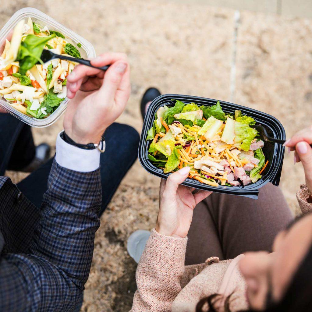 Två personer äter matlåda utomhus